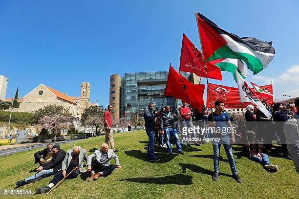 Palestinian refugees hold a placard and Palestinian flags during the commemoration the 40th Palestinian Land Day in front of UN Economic and Social...
