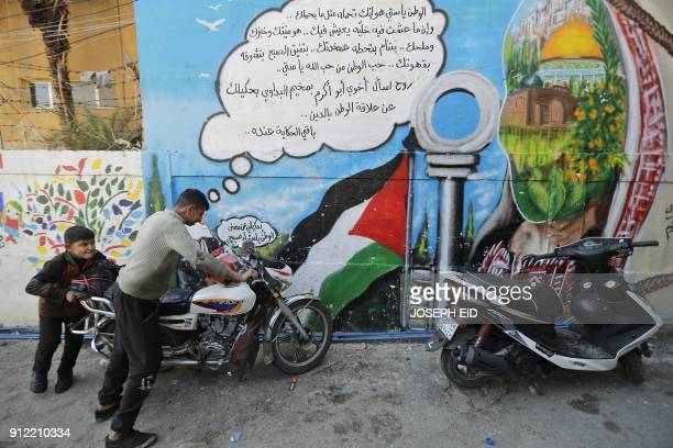 Palestinian refugees push a motorbike at the Shatilla Palestinian refugee camp, on the southern outskirts of the Lebanese capital Beirut, on January...