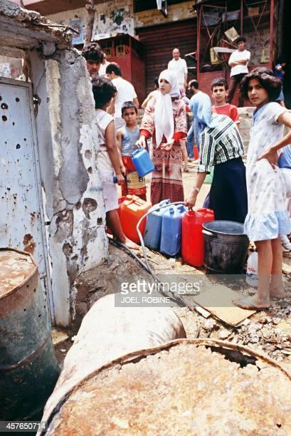 Palestinian refugees queue up for clean water in the camp of Shatila near Beirut 23 June 1985 Des réfugiés palestiniens font la queue pour...