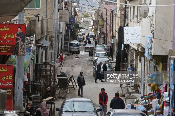Palestinian refugees walk on January 18 2018 at the alBaqa'a refugee camp some 20 kilometres north of Amman which was built as an emergency camp in...