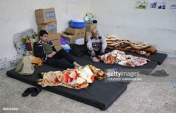 Palestinian refugees who fled the fighting in Syria's Yarmuk refugee camp are seen at a temporary makeshift shelter in the Tadamon neighborhood south...