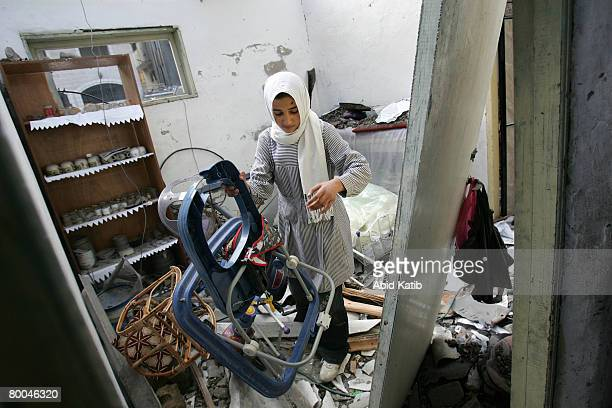 Palestinian relative of fivemonth old Mohammad Naser AlBuri carries his walker as she inspects the damaged of his family's home February 28 2008 in...