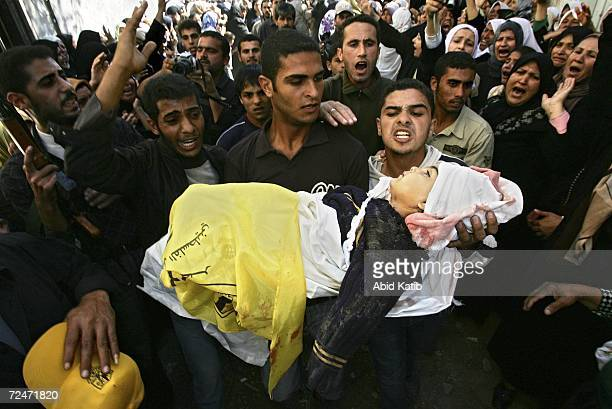 Palestinian relatives carry the body of baby Rima Athamna during the family funeral in Beit Hanoun town on November 9 2006 in Gaza Strip The families...