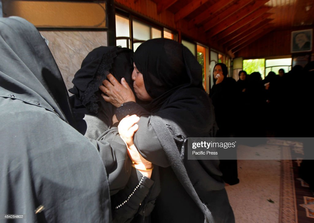 Palestinian relatives comfort each other after they saw the bodies of two Palestinian brothers Omar ,16, and Mohammed,12, Braim who were killed yesterday, before the open-ended ceasefire in the Gaza war between Israel and the Palestinians held on Wednesday in Khan Younis in southern Gaza strip.
