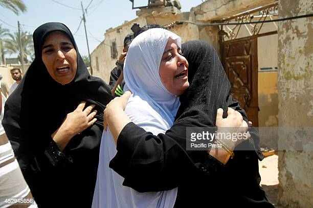 Palestinian relatives mourn during the funeral for fifteen members of the Abu zeid Duheir and alHashash families that were killed in an Israeli air...