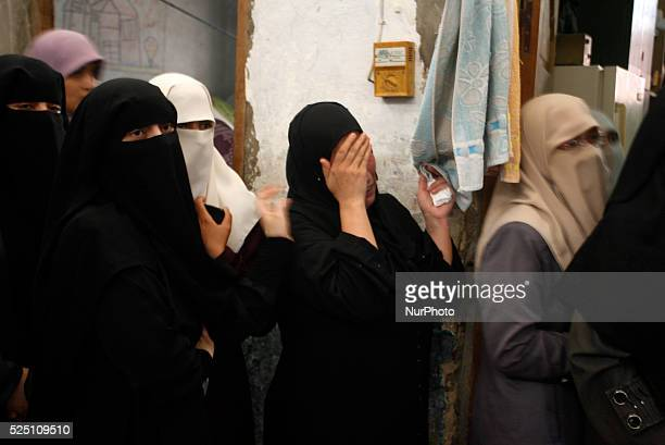 Palestinian relatives of eight members of the Al Haj family, who were killed in a strike early morning, grieve in the family house during their...
