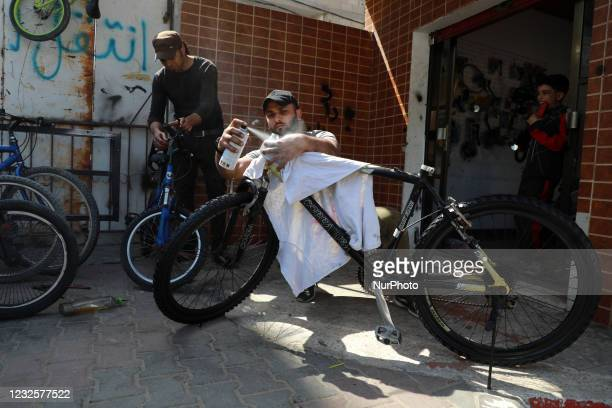 Palestinian repairs a bicycle tire at his workshop in Gaza city on April 28, 2021.