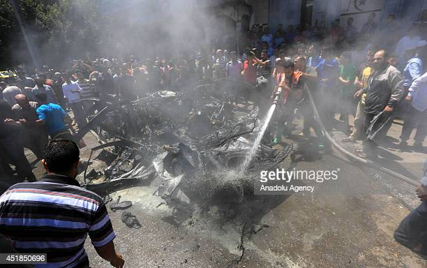 Palestinian rescue worker sprays water on the wreckage of a vehicle after it was hit by an Israeli strike in Gaza City, on July 8, 2014. The toll...