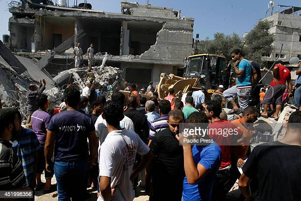 Palestinian rescue workers and residents inspect a building hit by an Israeli airstrike killing eight people in the southern Gaza Strip city of Khan...