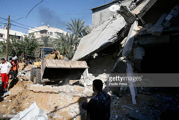 Palestinian rescue workers use a bulldozer to remove debris after an Israeli air strike in the town of Khan Yunis in the Gaza Strip. Israeli strikes...