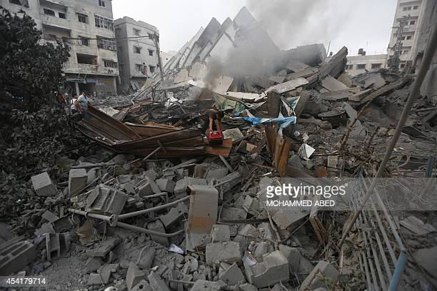 A Palestinian resident inspects the remains of AlBasha a building that was destroyed by an Israeli air strike in Gaza City on August 26 2014 An...