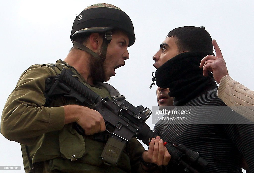 A Palestinian resident of the northern West Bank village of Madama argues with an Israeli soldier after security forces came to intervene in clashes between Palestinian farmers and Israeli settlers from the Yitzhar settlement, on December 17, 2012, in the Israeli-occupied West Bank, near Nablus.