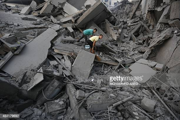 Palestinian residents inspect the remains of AlBasha a building that was destroyed by an Israeli air strike in Gaza City on August 26 2014 An Israeli...