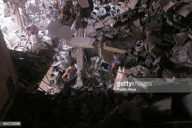 Palestinian residents salvage items from the remains of their homes that were destroyed by an Israeli air strike on Rafah town in the southern Gaza...