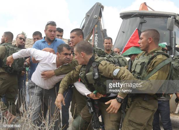 Palestinian resists to Israeli security forces as he tries to get the Palestinian flag while Palestinians gathered to block a road work by Jewish...