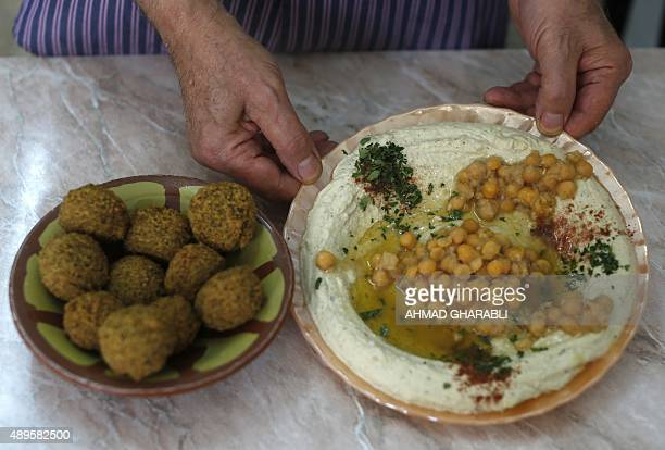 Palestinian restaurant owner Yasser Taha displays a plate of hummus a paste made from chickpeas and a bowel of falafel which are made from mashed and...