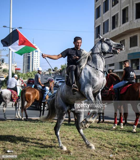 Palestinian rides a horse as he holds a Palestinian flag during a demonstration organized by Palestine Equestrian Federation to show solidarity with...