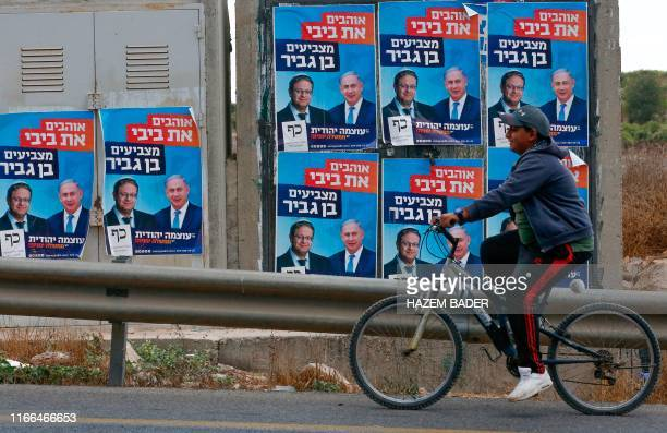 A Palestinian rides his bicycle past electoral campaign posters depicting Israeli Prime Minister Benjamin Netanyahu and far right politician Itamar...