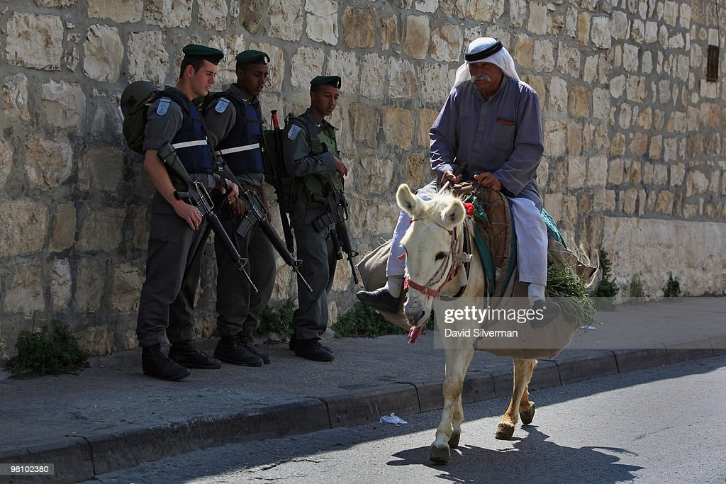 A Palestinian rides his donkey past Israeli police guarding the traditional Palm Sunday procession from the Mount of Olives to the Old City on March 28, 2010 in Jerusalem, Israel. Palm Sunday, which marks the start of Holy Week, is a landmark in the Christian calendar, marking the triumphant return of Jesus to Jerusalem the week before his death when a cheering crowd greeted him waving palm leaves.