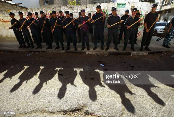 Palestinian riot police take up a position as they try to control a group of protesters outside the court hearing the trial of four Palestinian taxi...