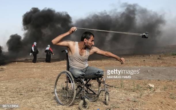 TOPSHOT Palestinian Saber alAshkar hurls rocks during clashes with Israeli forces along the border with the Gaza strip east of Gaza City on May 11 as...