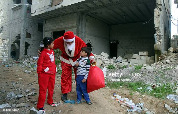 Palestinian Samih Vadi disguises himself as Santa Claus and hands out toys to the Palestinian children among the debris of buildings destroyed by...