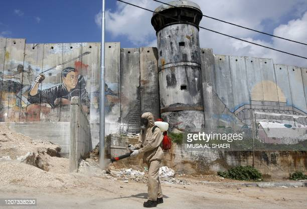Palestinian sanitary department worker sprays disinfectant on March 16, 2020 around the refugee camp of Aida, with Israel's controversial separation...