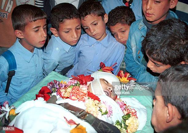Palestinian school boys look at the body of fouryearold Palestinian girl Reham Abu Taha who was hit by an Israeli bullet in her left eye two day...