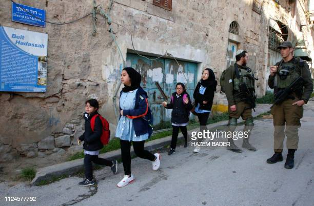 Palestinian school children walk past Israeli soldiers after forces closed a street near the Israeli settlement of Beit Hadassa in the divided West...