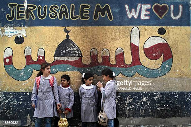 Palestinian school girls stand in front of a mural painted on their school wall in the Mediterranean beachfront alShati Palestinian refugee camp the...
