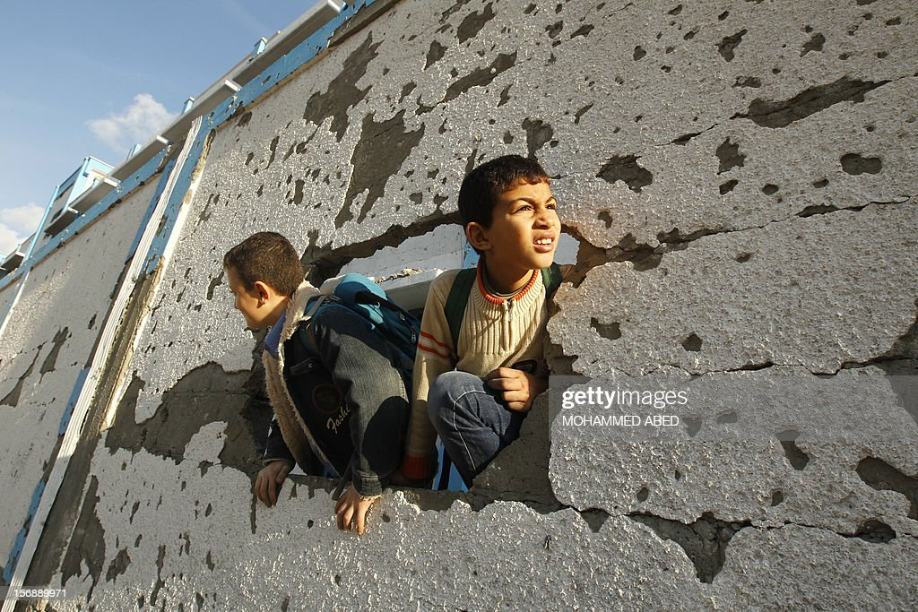 Palestinian schoolboys look through a hole at their damaged United Nations run school in Gaza City, on November 24, 2012, three days after a truce was declared between Israel and Hamas. Gaza's children, virtually absent from the streets since the violence, are beginning to return to school after a truce between Israel and Gaza's Hamas rulers ended eight days of deadly bombardment.