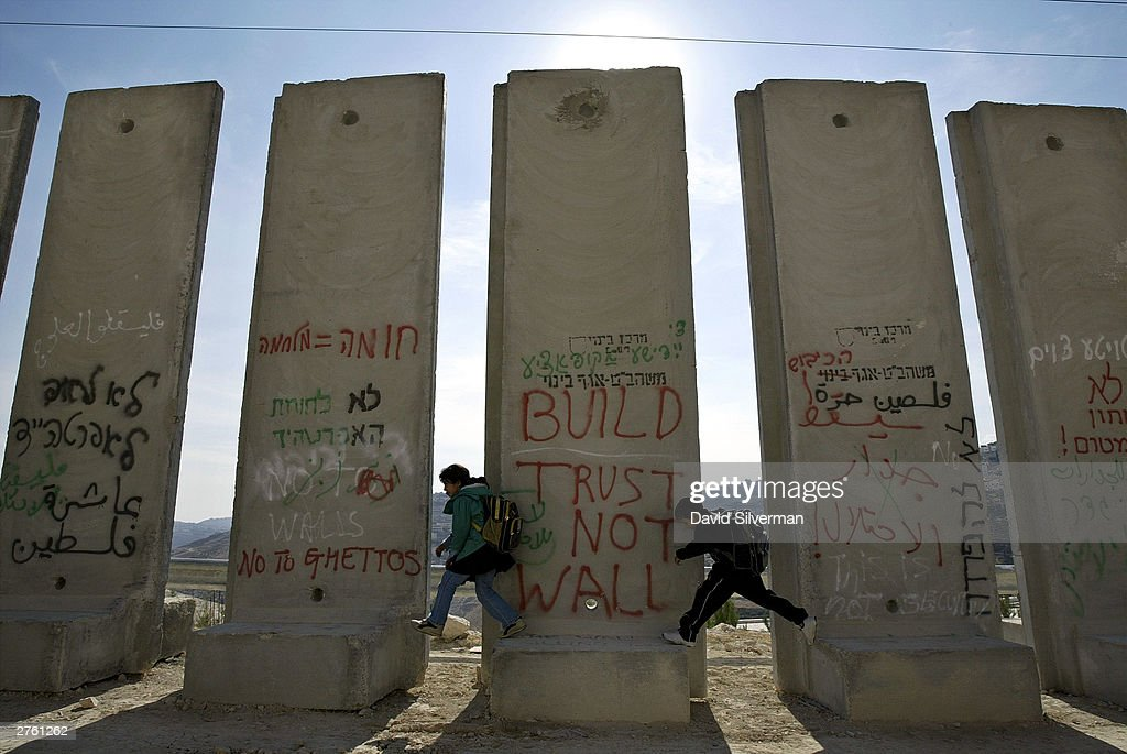 Palestinian schoolchildren play on graffiti-covered concrete blocks November 13, 2003, as they make their way home to the Arab East Jerusalem village of Sawahreh. Residents say that their village will soon be divided by Israel's separation wall, which will leave about a third of its population outside the barrier.