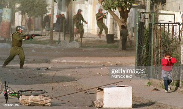 A Palestinian schoolgirl covering her ears 09 march 1993 in Gaza City while fleeing Israeli soldiers shooting at demonstrators during heavy clashed...
