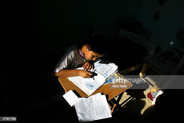 Palestinian schoolgirl Suha Hammad write her homework December 8, 2003 in the central Gaza Strip refugee camp of Deir al-Balah. Thousands of...