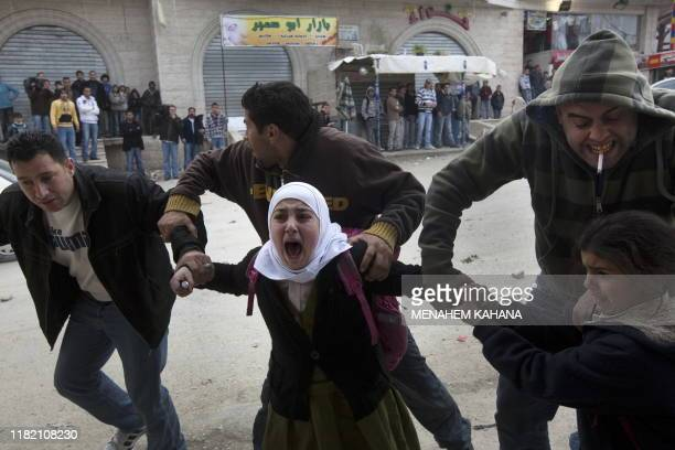 Palestinian schoolgirls are evacuated during clashes between Palestinian stone throwers and Israeli forces following an arrest operation at the...