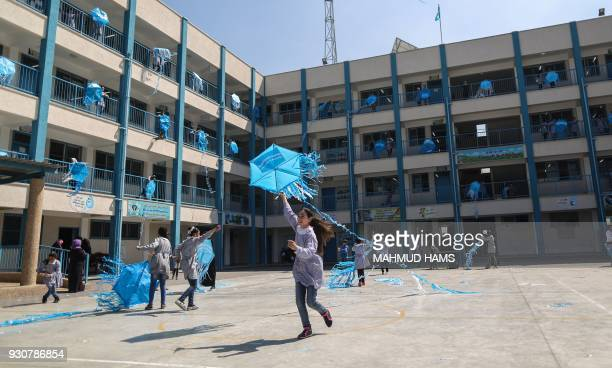 TOPSHOT Palestinian schoolgirls fly kites outside their classrooms at a school belonging to the United Nations Relief and Works Agency for...