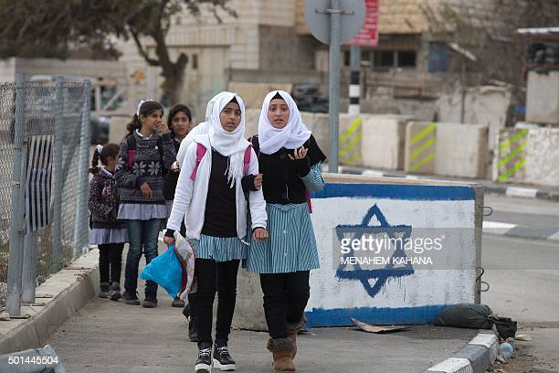 Palestinian schoolgirls pass by an Israeli army checkpoint with an Israeli flag painted on a concrete block in the West Bank city of Hebron on...