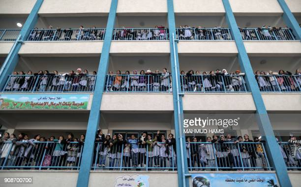 TOPSHOT Palestinian schoolgirls pose for a group picture outside their classrooms at a school belonging to the United Nations Relief and Works Agency...
