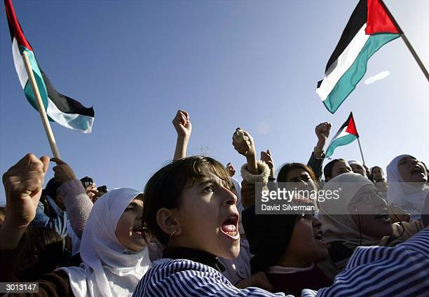 Palestinian schoolgirls shout slogans during a protest of the construction of Israel's security fence February 25 2004 on land from their West Bank...