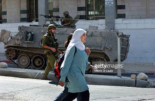 Palestinian schoolgirls walk past an Israeli armored vehicle and Israeli soldiers on patrol September 28 2002 in the West Bank town of Ramallah...