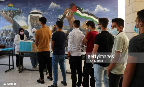 Palestinian secondary students wait before taking their first Pfizer-BioNtech Covid-19 coronavirus vaccine, in Taffuh village, west the West Bank...