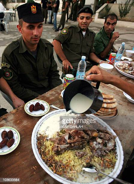 Palestinian security forces and citizens prepare to break their daylong Ramadan fast over a group 'Iftar' meal of traditional Mansaf at the police...