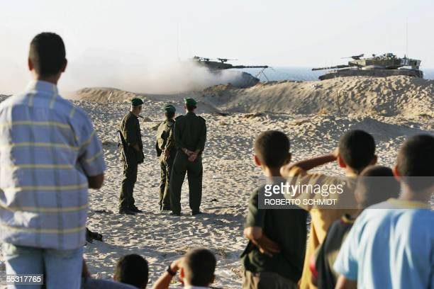 Palestinian security forces and residents watch Israeli tanks manever on the border zone between the southern Gaza Strip town of Khan Yunes and the...