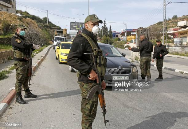 Palestinian security forces man a checkpoint at one of the entrances to the West Bank city of Bethlehem on March 10, 2020 currently under lockdown...