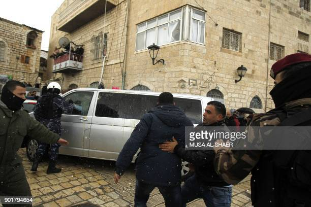 Palestinian security forces push away protesters from the convoy of Jerusalem's Greek Orthodox patriarch Theophilos III on its way to the church of...