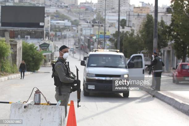 Palestinian security forces take measures at entrance and exit of quarantined Beitunia town within coronavirus precautions in Ramallah West Bank on...