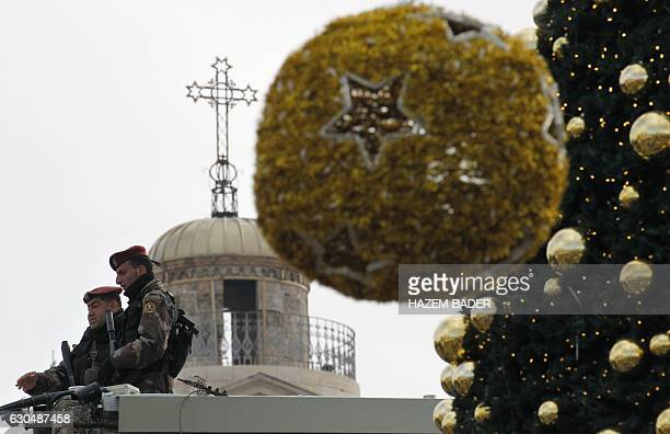 Palestinian security members stand guard as Christian scouts perform at the Manger Square outside the Church of the Nativity during Christmas...