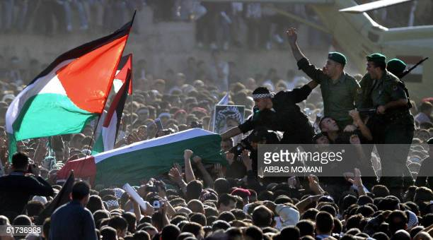 Palestinian security men carry the coffin of veteran Palestinian leader Yasser Arafat across the crowd inside the Mouqataa compound Yasser Arafat's...