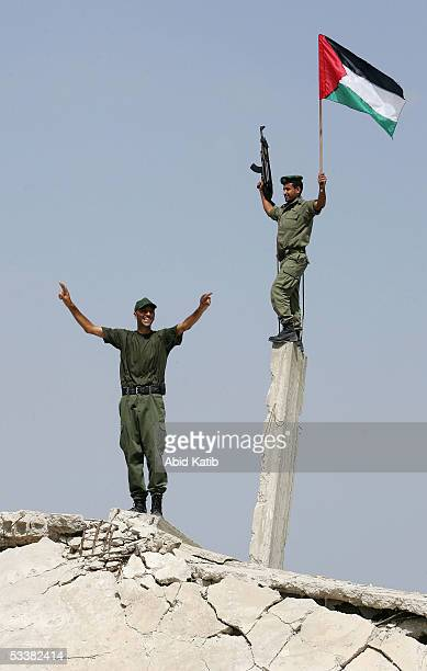 Palestinian security men wave their national flag near the Rafah refugee camp border with Egypt on August 13, 2005 in southern Gaza strip. As Israel...