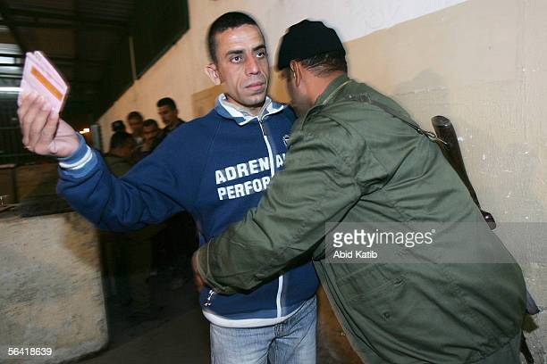 Palestinian security officers check workers before allowing them to cross into Israel at the Erez checkpoint outside the northern Gaza town of Beit...